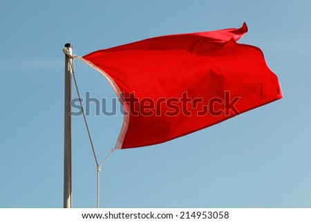 Red flag on a beach waving above blue sky