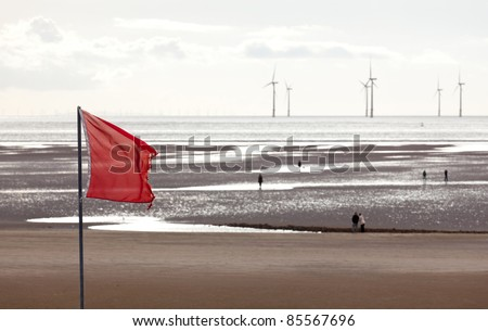 Red flag warns swimmers as wind turbines turn in the ocean off a sandy beach near Liverpool on a cold and cloudy day