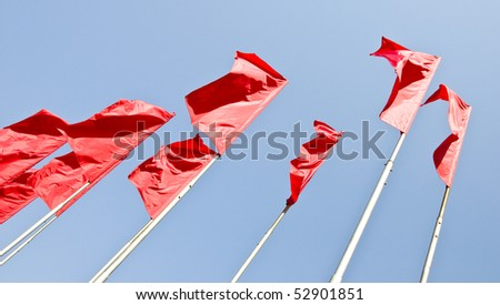 Red flags fluttered in the wind. Against the background of blue sky.