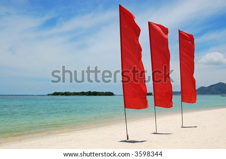 Red flags on white sand beach