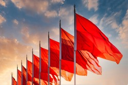 Red flags, the symbol of the Chinese communist party blow in the wind in the center of Beijing Tiananmen Square. Sunset sky in background with no recognisable buildings.