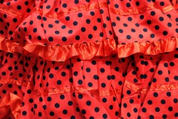 red flamenco fabric cloth with black polka dots and ruffles for background - typical symbol of Seville or Andalusia in Spain
