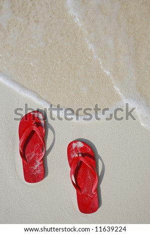 Red Flip flops on a tropical beach with gentle wave