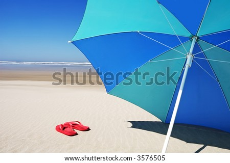 Red flip flops under a beach umbrella - stock photo