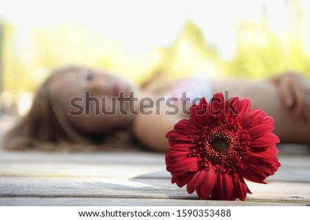 Red flower with girl in background