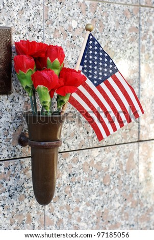 Red flowers and a small American flag at cemetery crypt.