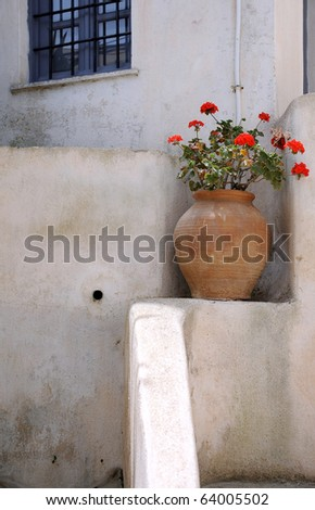 Red flowers in large ceramic brown vase at the house in the village of Pyrgos, Santorini archipelago, Greece