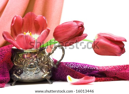 red flowers in vase with fabric