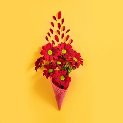 Red flowers on a yellow background. A bouquet of chrysanthemums in a waffle cup. Valentine's day concept.