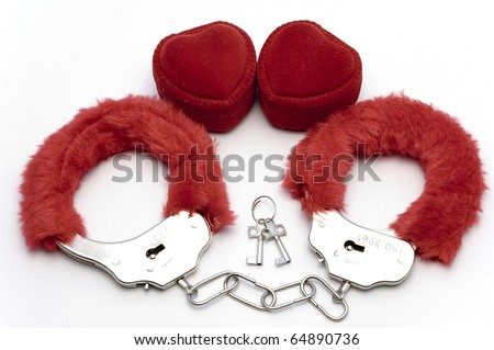 Red fluffy handcuffs with hearts on a white bacground