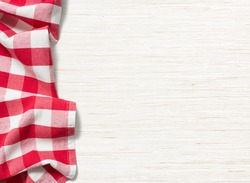 red folded tablecloth over bleached wooden table