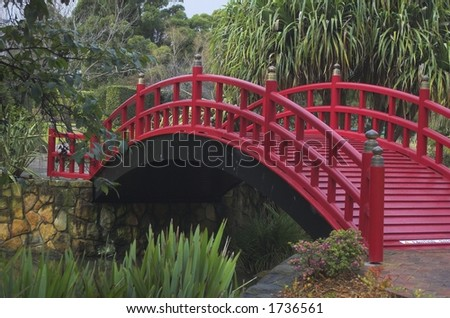Red footbridge over a stream flowing through a Japanese garden