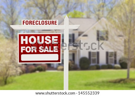 Red Foreclosure Home For Sale Real Estate Sign in Front of House. stock photo