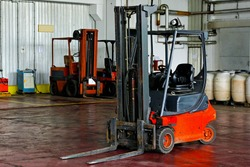 Red forklift parked in modern factory warehouse