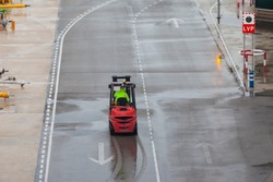 Red forklift rides on the road at the airport in the rain, autoloader