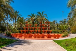 Red fountain inside of El Palmeral municipal park in Elche, Spain