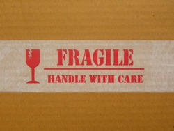 Red Fragile Handle With Care text on sticker on brown cardboard box
