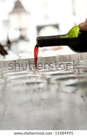 Red French wine pour from a bottle in the glasses which are standing in a row