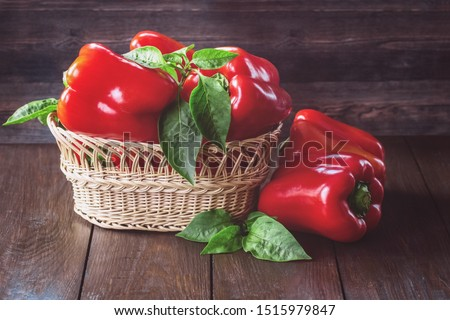 red fresh paprika peppers and green leaves in a wicker basket close-up. fresh red paprika on wooden background. background with paprika. Stockfoto ©