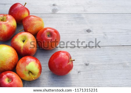 Red fresh shiny apples on grey weathered wooden table background with copy space for text. Freshly harvested sweet tasty fruit as healthy snack or prepare for delicious salad cooking or bakery.  #1171315231