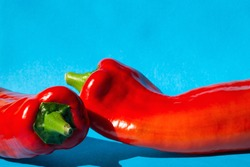 Red Fresh Sweet Peppers marconi on blue background, retro modern design close-up