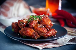 Red fried korean chicken on dark background
