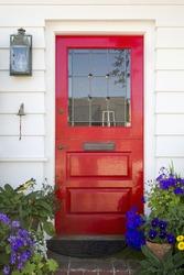 Red front door of an upscale home/Vertical shot of a red front door on a home with a mail slot, plants, doorbell, brick flooring and reflection in the window.