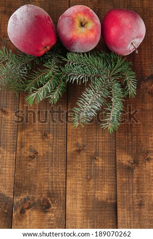 Red frosted apples with fir branch on wooden background