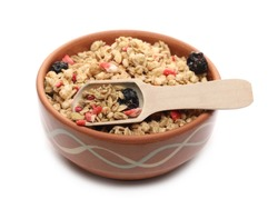 Red fruits cereal mix in clay bowl with wooden spoon, fruity and crunchy muesli with dried raspberry, strawberry, cherry chunks isolated on white background