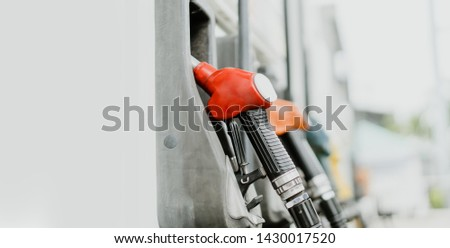 Red fuel nozzle in Gas station.Fuel dispensing pump,Horizontal shot of some fuel pumps at a gas station.