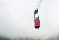 Red funicular or red suspension cable car to Lomnicky peak in fog or clouds, High Tatry, Slovakia