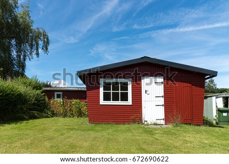 Red garden shed with white door on a sunny day