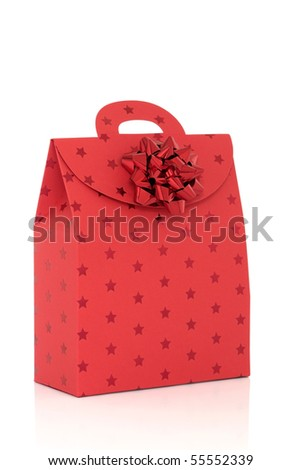 Red gift bag with star pattern and bow isolated over white background.