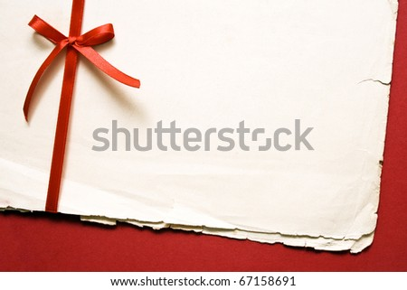 Red gift bow with ribbons and blank old paper on red paper