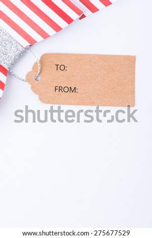 Red gift bow with stripes and cardboard tag over the white background, isolated