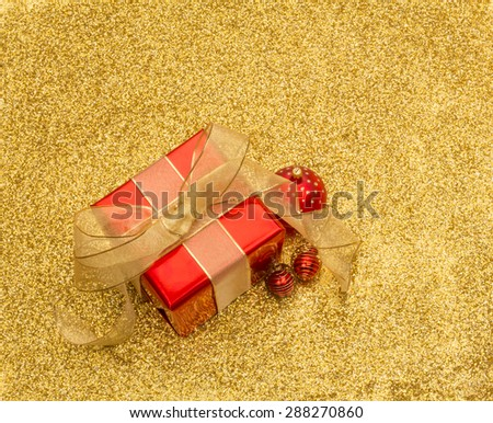 Red gift box and baubles with gold ribbon on a gold glitter background with copy space
