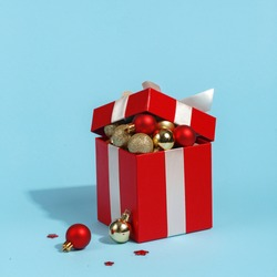 Red gift box filled with Christmas toys. Christmas creative minimal concept