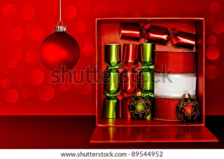 Red Gift Box Filled With Red & Green Party Favors, Decorative Red & White Ribbon And Red, Green & Gold Glitter Christmas Ornaments Over Red Textured Background With LED Lights