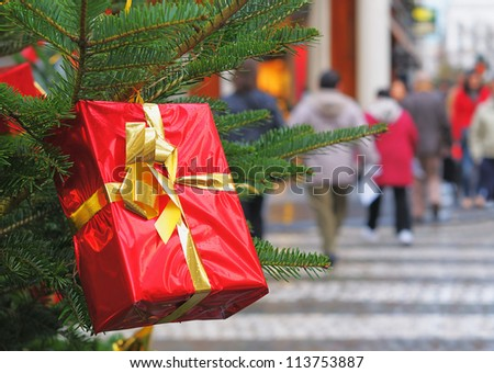 Red gift box for Christmas with golden stripe on New Year tree on the street and blurred silhouettes of people