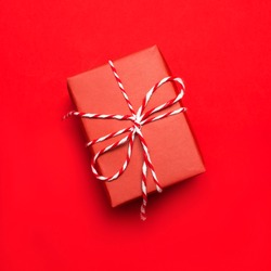 Red Gift box on red background top view flat lay. Holiday concept, birthday gift, new year or Christmas gift box presents Xmas holiday. Congratulations background
