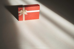 Red gift box with a light ribbon bow on a white background in the rays of soft light against the shadow. Gift wrapping of jewelry and bijouterie, engagement