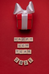 Red gift box with a white ribbon on a red background under the inscription of wooden blocks