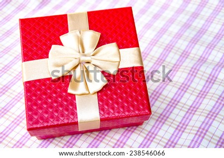 red gift box with gold ribbon on table background.