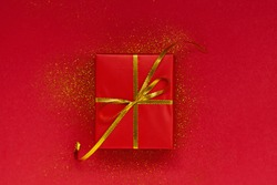 Red gift box with golden bow on red background with sparkles. Christmas and holiday concept.