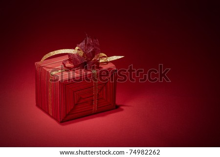 Red gift box with golden ribbon on red background