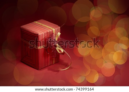 Red gift box with golden ribbon on red blurred background