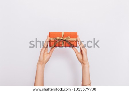Red gift box with ribbon in female hands over head on white background - Shutterstock ID 1013579908