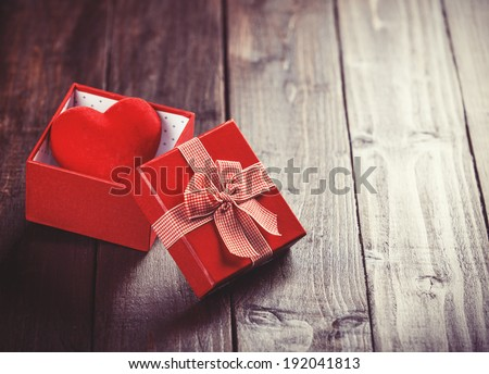 Red gift box with toy heart inside on wooden table. Photo in retro color image style.