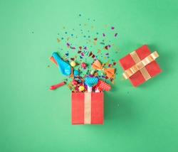 Red gift box with various party confetti, balloons, streamers, noisemakers and decoration on a green background. Colorful celebration background. Flat lay.