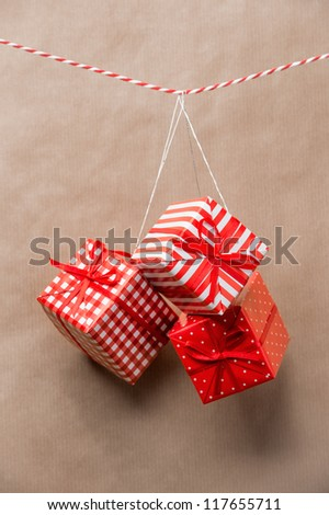 Red gift boxes hanging on a ribbon. Old brown paper background